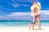 Young loving couple relaxing on sand tropical beach on blue sky  — Stock Photo
