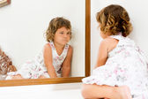Young beautiful child girl looking at herself in mirror at home — Stock Photo