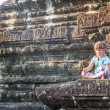 Young happy child girl tourist meditating in angkor wat, cambodi — Stock Photo #67300443