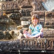 Young happy child girl tourist meditating in angkor wat, cambodi — Stock Photo #67300545
