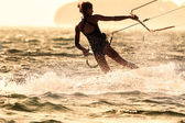 A young woman kite-surfer rides against the sun — Stock Photo