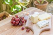 Different types of cheese with wine and grapes on natural backgr — Stock Photo