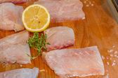 Fresh raw fish slices with lemon on wooden cutting board — Stock Photo
