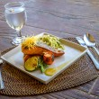 Grilled salmon steak served with pasta and vegetables in a small — Stock Photo #70448959