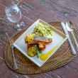 Grilled salmon steak served with pasta and vegetables in a small — Stock Photo #70449353