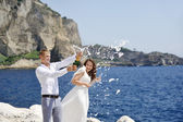 Young married couple uncorking champagne bottle by the sea after their wedding — Stock Photo