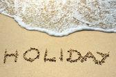 Holiday written on the sand beach near sea — Stockfoto