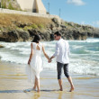 Bride and groom walking together holding hands near sea, Sperlonga — Stock Photo #60890913