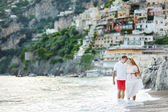 Smiling happy young couple walking on Positano beach — Stock Photo