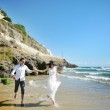 Happy couple holding hands running on the beach near sea in wedding day — Stock Photo #64313251