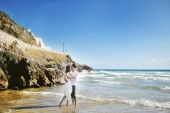 Bride and groom kissing on the beach in wedding day in Italy — Stockfoto