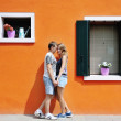 Happy couple holding hands near orange colored wall in Burano, Venice, Italy — Stock Photo #67574697