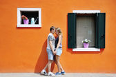 Happy couple holding hands near orange colored wall in Burano, Venice, Italy — Stock Photo