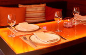 Glass dining table with orange backlight — Stock Photo