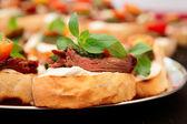 Bruschettas with beefsteak and pesto sauce — Stock Photo