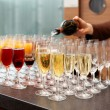 Bartender is pouring sparkling wine in glasses — Stock Photo #59338279