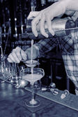 Bartender is straining drink in a glass — Stock Photo