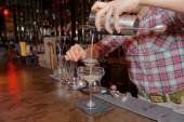 Bartender is straining drink in glass — Stock Photo