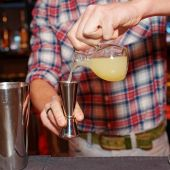 Barman is pouring orange jucie in jigger — Stock Photo