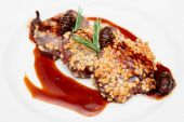 Venison fillet fried with pine nuts in plate — Stock Photo