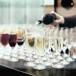 Bartender is pouring sparkling wine in glasses, toned — Stock Photo #65494171