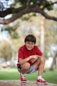 Young boy sitting on a table in the park — Stock Photo