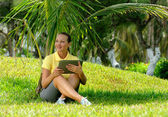 Young woman using tablet outdoor laying on grass, smiling. — Stock Photo