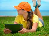 Young woman using tablet outdoor laying on grass — Stock Photo