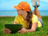 Jonge vrouw met behulp van tablet pc buiten opleggen van gras — Stockfoto
