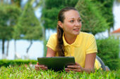 Young woman on the lawn under a palm tree with her tablet comput — Stock Photo