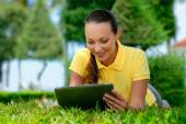 Young woman lying on the lawn with a tablet computer — Stock Photo