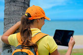 Side view of young woman in cap on the outdoor with  tablet comp — Stock Photo