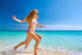 Couple Running Through Waves On Beach Holiday — Stock Photo