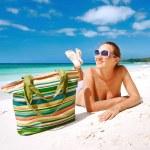 Smiling beautiful woman sunbathing on a beach — Stock Photo #66715599