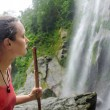 Tired, but happy young woman hiker looking at a waterfall jungle — Stock Photo #71701585