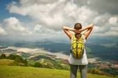 Portrait of happy traveler woman with backpack standing on top o — Stock Photo