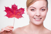 Skin care. Portrait of young woman girl with red maple leaf. — Stock Photo