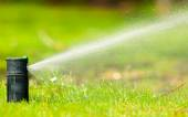 Gardening. Lawn sprinkler spraying water over grass. — Foto de Stock