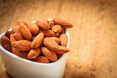 Almonds in bowl on wooden background — Stock Photo