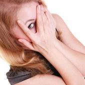 Shy afraid woman peeking through fingers isolated. — Stock Photo