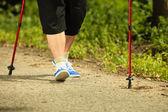 Active woman senior nordic walking in park. legs — Stock Photo