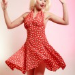 Beautiful pinup girl in blond wig and retro red dress dancing. Party. — Stock Photo #52078647