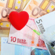 Cost of health care: red heart syringe on euro money — Stock Photo #52078699