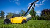 Gardening. Mowing lawn with yellow lawnmower — Foto de Stock