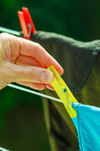 Woman hand hanging wet clothes on rope line — Stock Photo