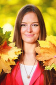 Fall season. Portrait girl woman holding autumnal leaves in park — Stock Photo