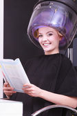 Girl relaxing reading magazine hairdryer by hairstylist in hair beauty salon — Stock Photo