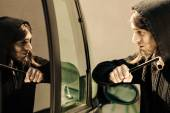 Transportation and crime- thief breaking car window — Stock Photo