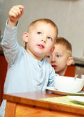 Two brothers boys kids children eating corn flakes breakfast morning meal at home. — Stock Photo