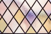 Stained glass with multi colored diamond pattern as background — Stock Photo
